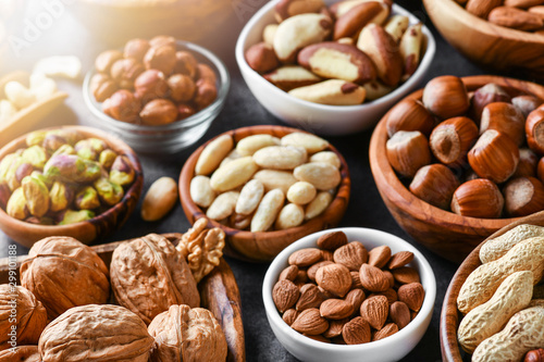 obraz lub plakat Mixed nuts in wooden bowls on black stone table. Almonds, pistachio, walnuts, cashew, hazelnut. Top view nut photo.