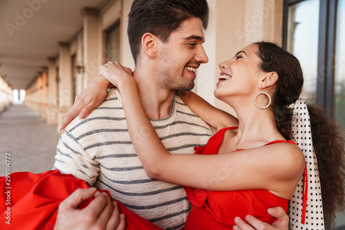 Obraz Image closeup of happy romantic man carrying woman in hands and laughing - fototapety do salonu