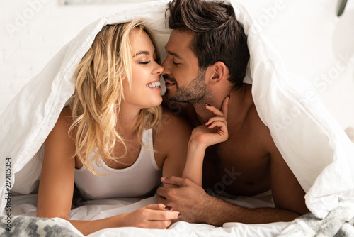 smiling couple going to kiss under sleeping sheets in the morning Fototapet