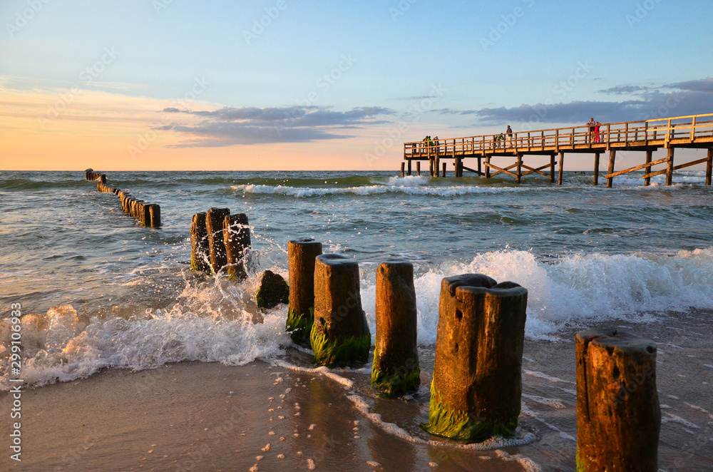 Fototapeta Wooden pier and breakwater during sunset over the Baltic Sea, Uniescie, Poland.