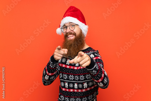 Fotografie, Obraz  Christmas man with long beard over isolated red background points finger at you