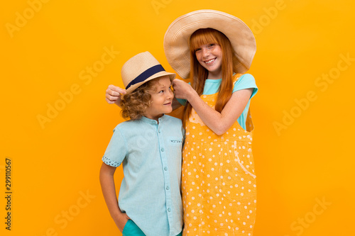 Fototapeta two beautiful children on an orange background stand hugging obraz