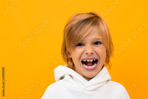 a boy in a white T-shirt on the background of an orange wall screams