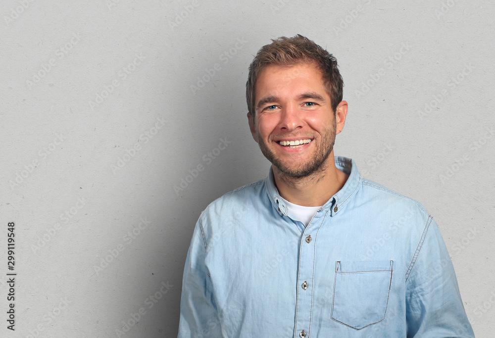Fototapeta Young man in denim shirt is smiling