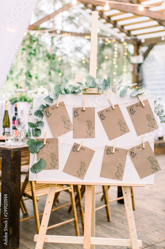 Decorated seating plan for wedding guests in woodent tent restaurant outdoors Fototapeta