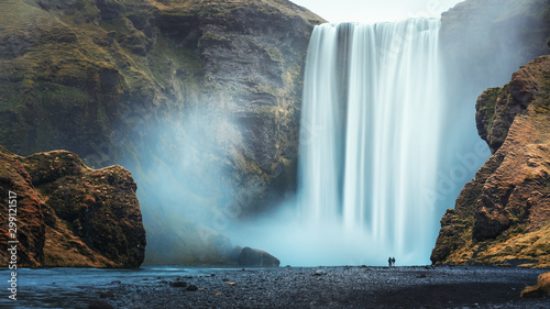 Couple of tourist near famous Skogafoss waterfall, Iceland Fototapete