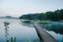 Fog, Grass, Trees Against The Backdrop Of Lakes And Nature. Fishing Background. Misty Morning. Nature. Wild Areas. Bridge Over The River The Island. Tent, Umbrella. Swamp.