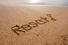 """Reset"" Message Written In Sand"