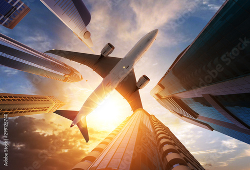 fototapeta na ścianę Commercial airplane flying above skyscrapers