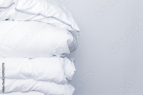Stampa su Tela  Pile of white bedding items, pillows and a blanket on white background with copy