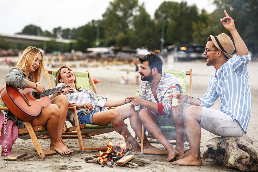 Fototapety, obrazy: Group of friends sitting by the camp fire at the beach.they singing and play guitar.Autumn season.