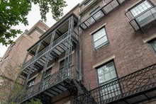Elaborate Balcony Railings On The Face Of Old Brick Apartment Buildings, View Looking Up, Horizontal Aspect