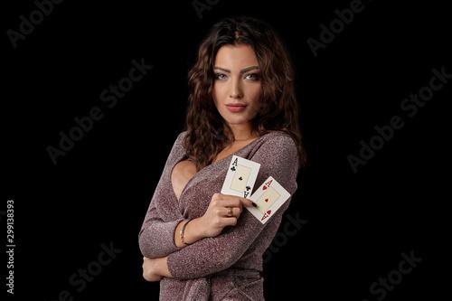 Obraz na plátně Brunette girl wearing shiny dress posing holding two playing cards in her hands standing against black studio background