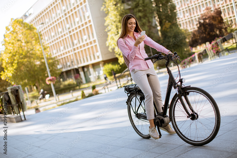 Fototapeta Young woman riding an electric bicycle and using mobile phone in urban environment