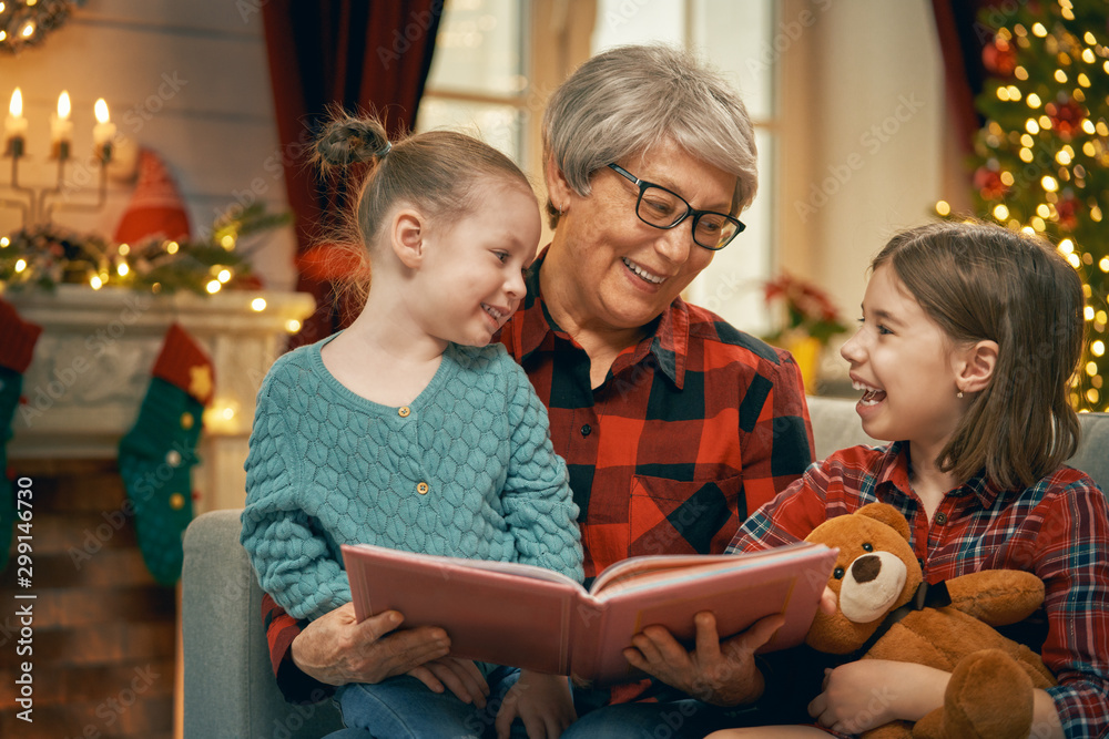 Fototapety, obrazy: Grandmother reading  to granddaughters near Christmas tree.