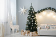 A beautiful Christmas tree stands in the interior of the living room with a sofa and a deer with lights