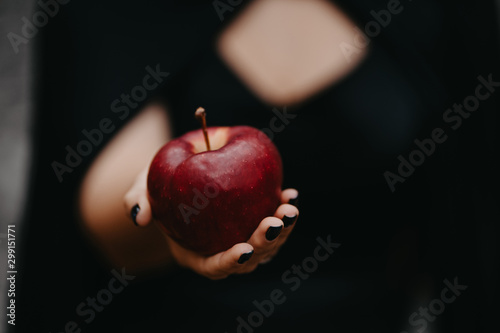 Obraz na plátně Female hand holds out red apple