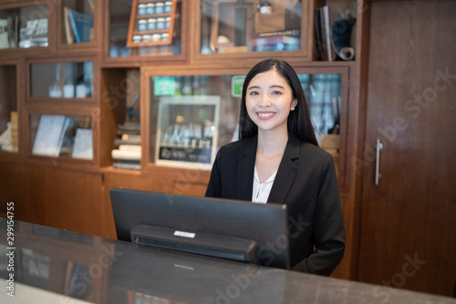 Welcome to the hotel,Happy young Asian woman hotel receptionist worker smiling s Fototapeta