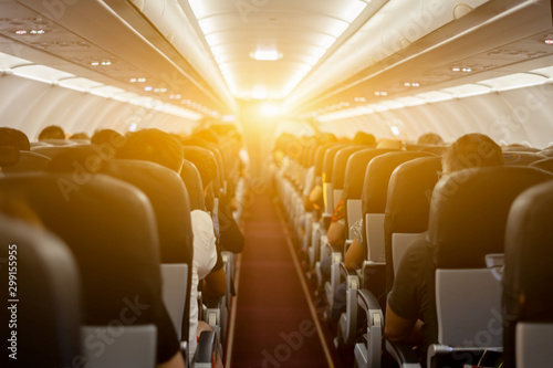 Air hostesses and passenger seat, Interior of airplane with passengers sitting on seats and welcomer stewardess walking the aisle in background. Travel by plane concept,vintage color,selective focus