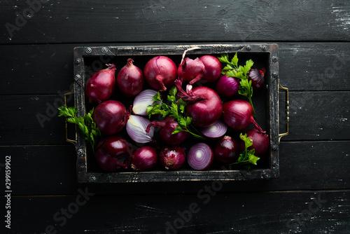 Fotografía  Purple onion in wooden box on black background
