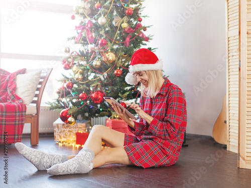 Foto auf Gartenposter Akt Woman using tablet in front of christmas tree