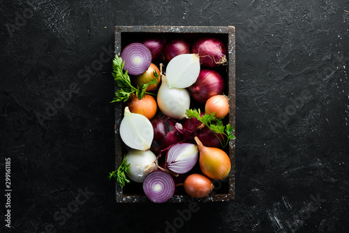 Foto Fresh ripe onions in wooden box on black background