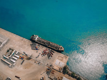 Drone View Of The Oil Tanker At The Quay, Pumping Fuel Into Numerous Petrol Trucks Through Gas Pipes; Technology Concept.