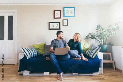 Fototapeta Young couple doing shoppings online on the sofa at home with laptop, looking at each other and smiling obraz