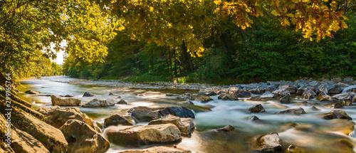 Foto Herbstpanorama am Fluss mit goldenen Sonnenstrahlen