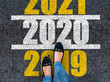 canvas print picture - happy new year 2020. lets start 2020. woman legs in shoes walks on asphalt road next to number 2020 and 2021. She is standing on number 2019.