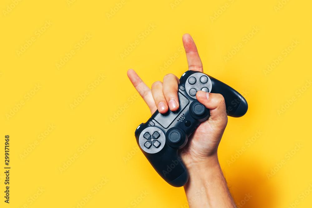 Fototapeta Man hand holding black gamepad