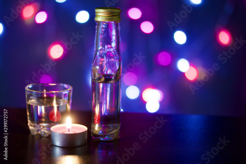 Fotografía  Burning candle with a drink on the background with colorful lights