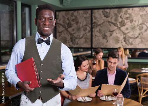 Obraz na plátně  Polite African American male administrator standing in restaurant hall, welcomin