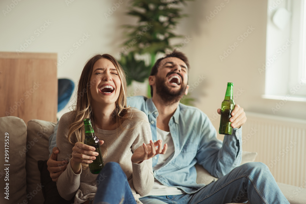 Fototapeta Happy couple having fun while drinking beer at home