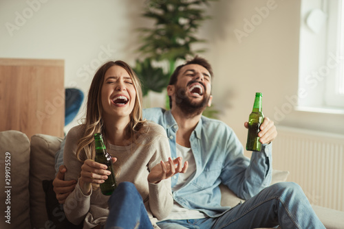 Happy couple having fun while drinking beer at home