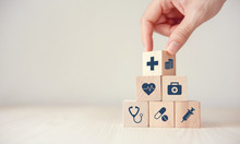 Health Insurance Concept, Hand Arranging Wood Cube Stacking With Icon Healthcare Medical On Wood Background, Copy Space, Financial Concept.