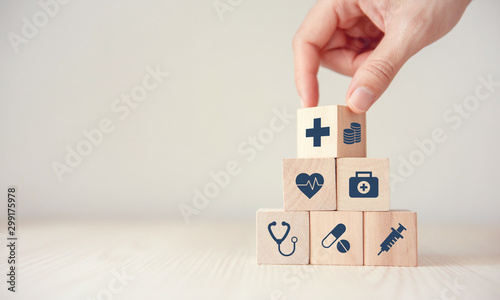 Fotografia  Health Insurance Concept, Hand arranging wood cube stacking with icon healthcare medical on wood background, copy space, financial concept