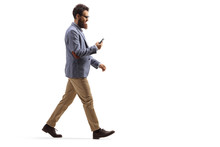 Bearded Man Walking And Looking At His Mobile Phone