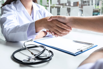 Doctor and patient shaking hands after checking with consultation and diagnosis to treatment talking about medical examination results in the clinic room