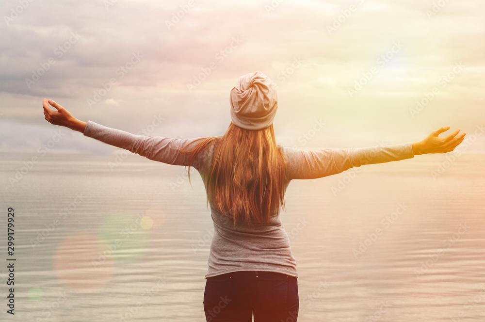 Fototapety, obrazy: A beautiful girl stands on the shore with her back to the camera. Hands up. Sunset. Yoga classes.