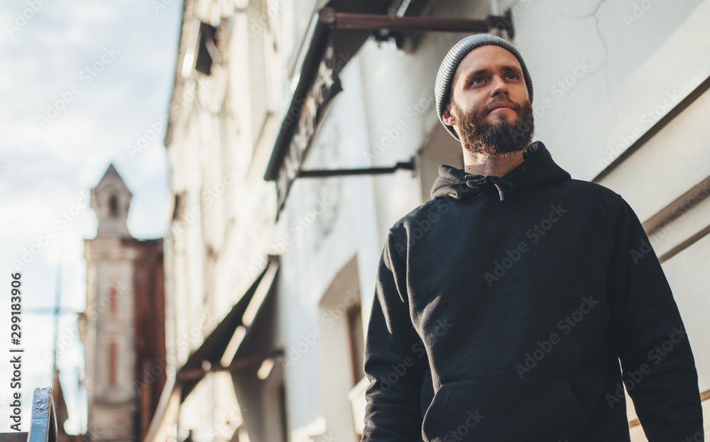 Fototapety, obrazy: City portrait of handsome hipster man with beard wearing black blank hoodie or hoody and hat with space for your logo or design. Mockup for print