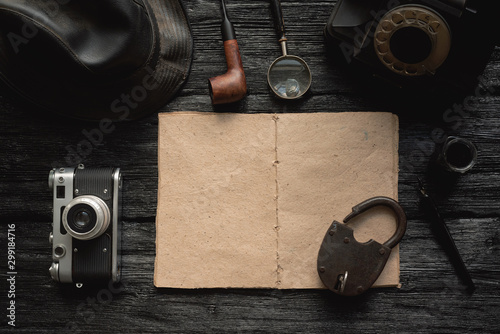 Open blank page detective book with various equipment around on black wooden table background Tablou Canvas