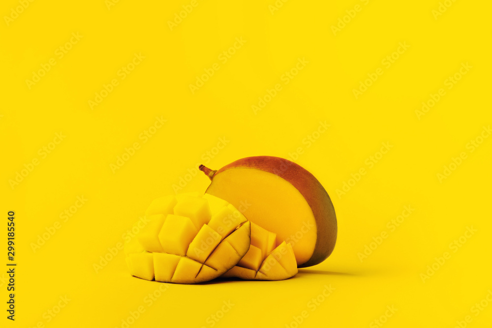 Fototapety, obrazy: mango fruit with mango sliced cubes on yellow background with space for text.