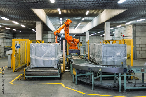 Fotomural  Robot Hand manipulator packaging factory products from conveyor into container