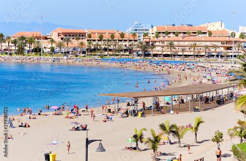 People sunbathing on sandy beach of Playa de los Cristianos, enjoy warm Atlantic Fototapeta