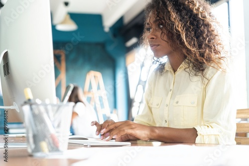Fotografía  Young african american businesswoman sitting in the office and working on laptop