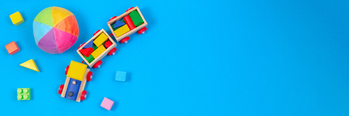 Baby kids toys banner background. Wooden train, soft ball and colorful blocks on blue background