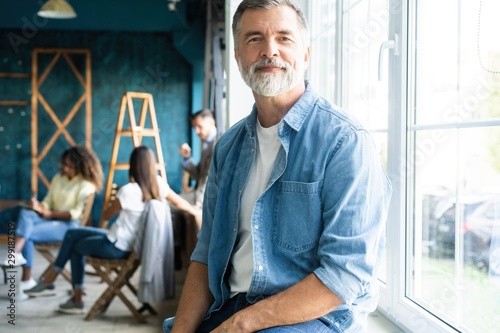 Smiling aged company boss posing in office