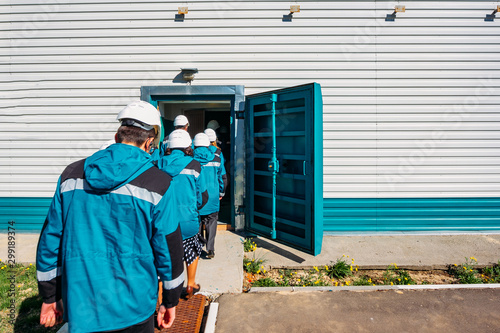 Factory workers entering to armored door of bomb shelter Canvas Print