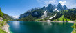 Famous Lake Gosau and Gosaukamm with Mount Dachstein. Spring is here! The snow is melting and spring brings the luscious green back to nature. The sun is about to hide behind the high peaks.